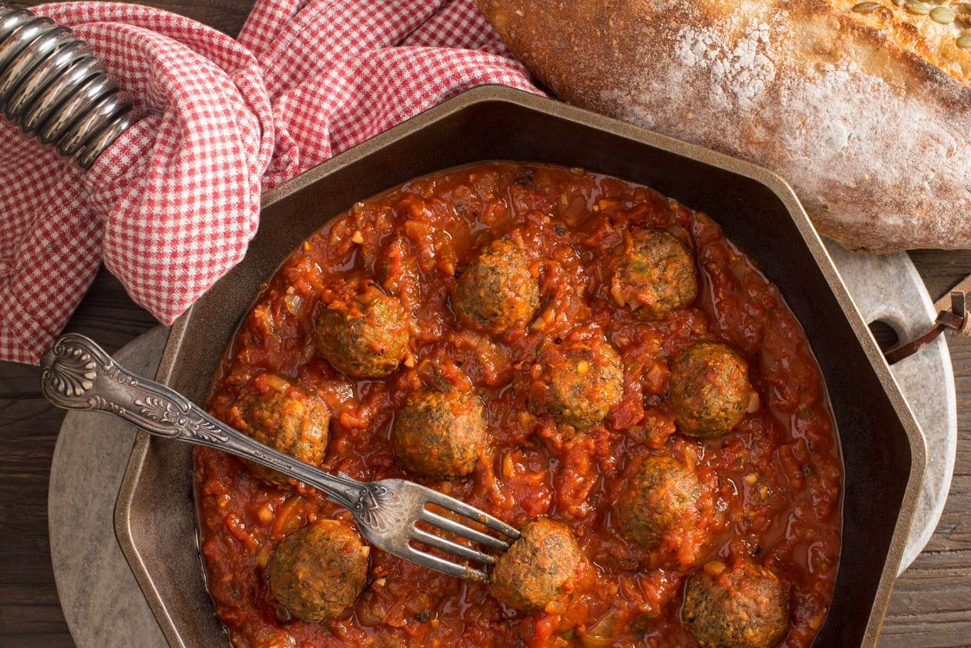 Italian style lentil meatballs with marinara sauce in pan next to loaf of bread