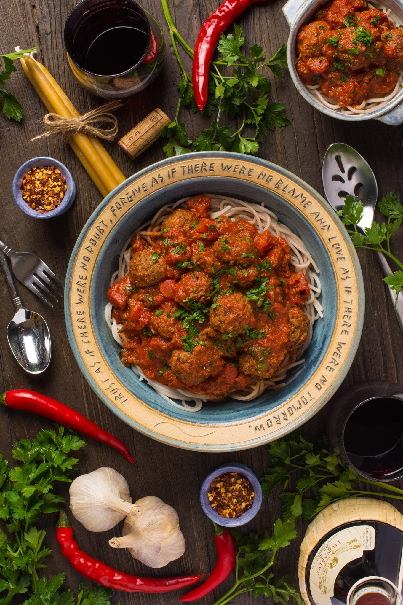 Italian Style Lentil meatballs in marinara sauce in bowls next to wine and fresh vegetables