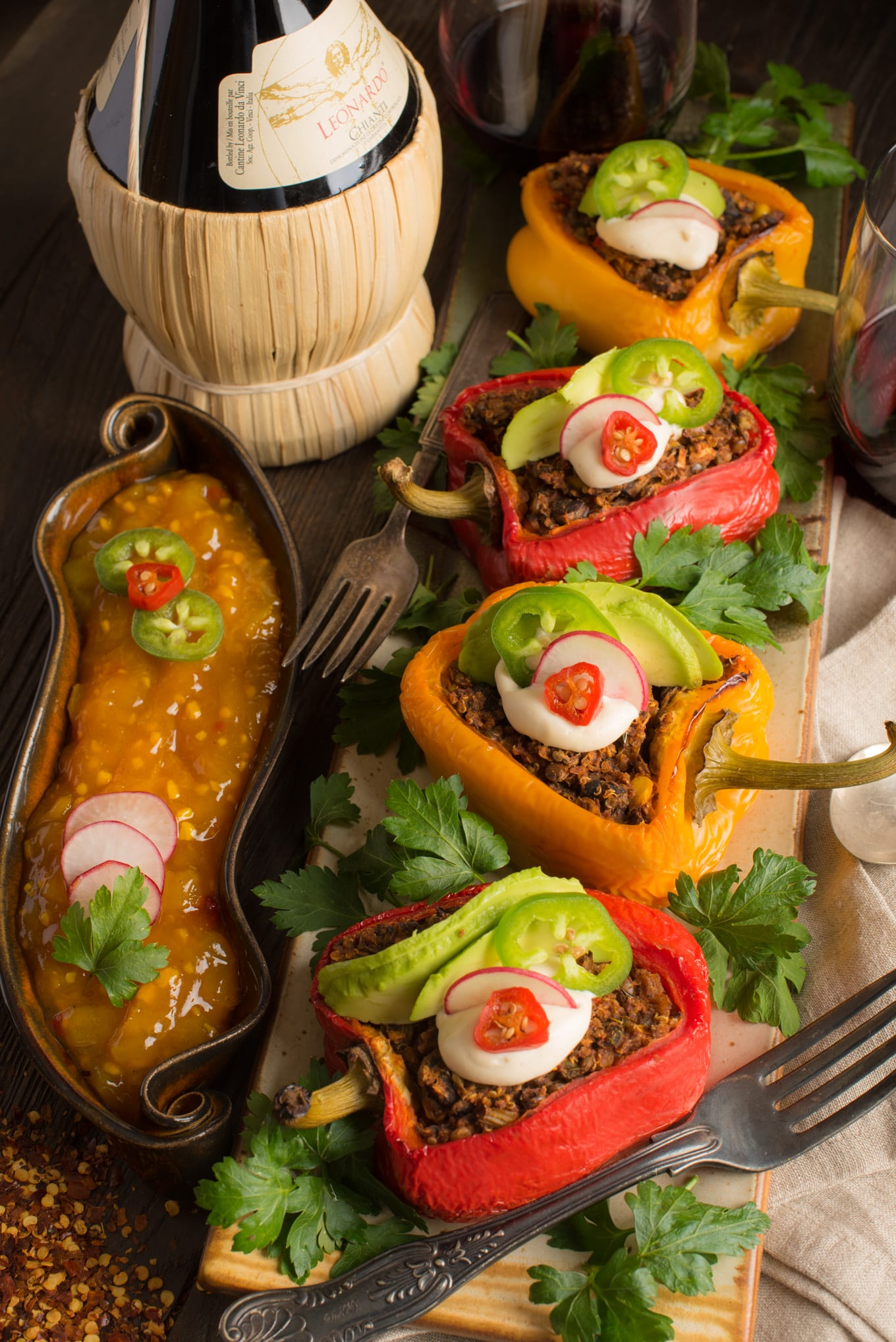mexican-inspired stuffed peppers on tray with chutney and bottle of wine