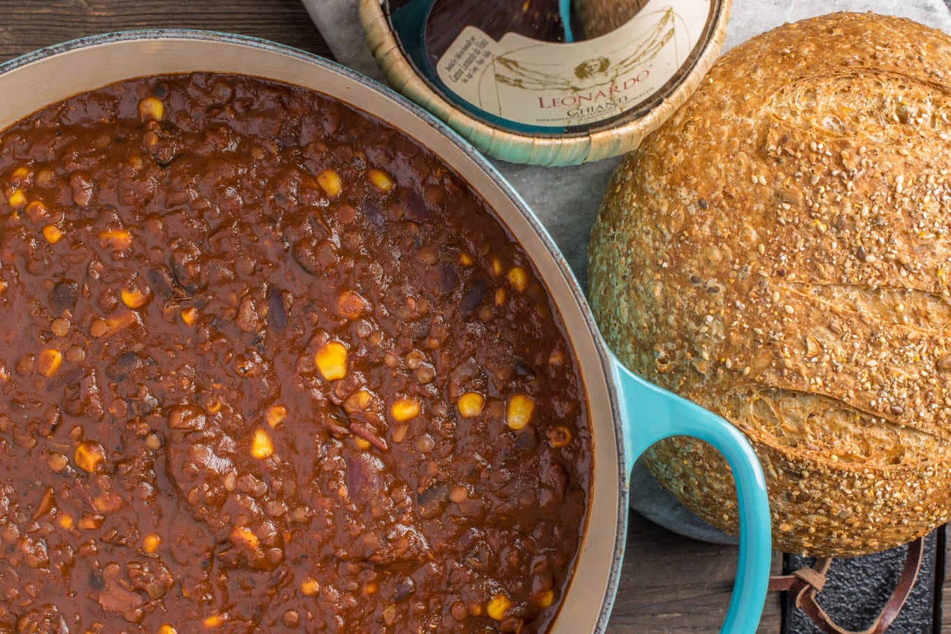 vegan mexican chili in pot with loaf of bread next to it