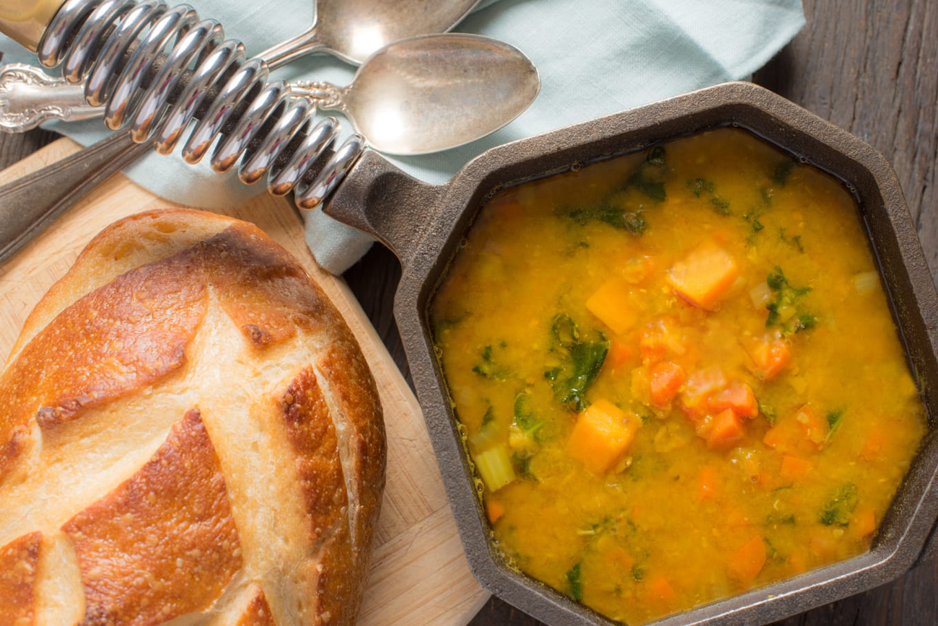 spiced lentil soup in small pot next to loaf of bread