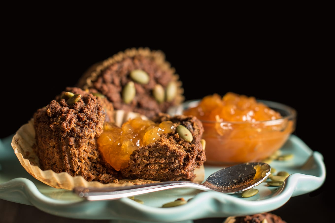 two pumpkin spice muffins with small bowl of apricot jam on cake stand