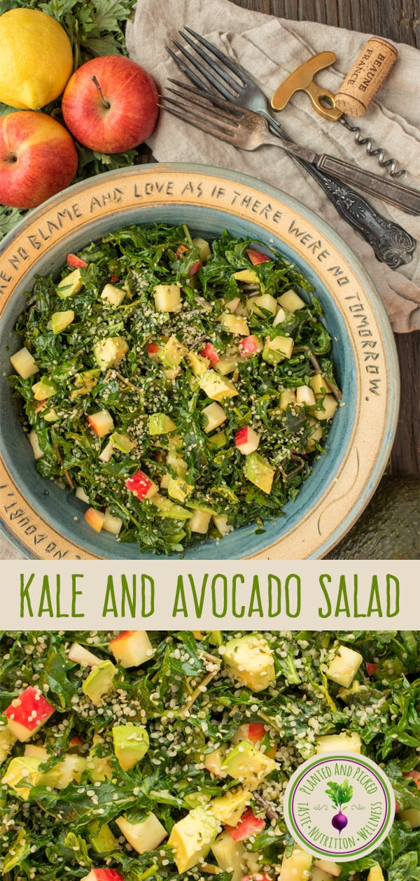 kale and avocado salad in bowl next to forks and apples and lemon