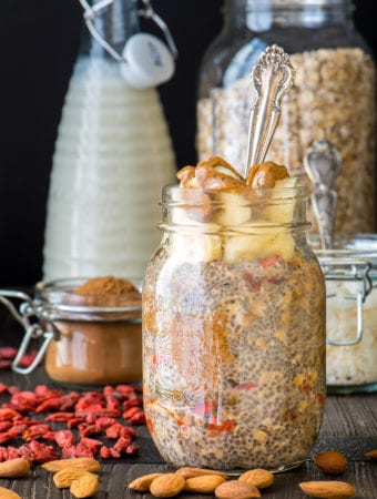 nut butter overnight oats in jar with almond milk and oats in jars in background