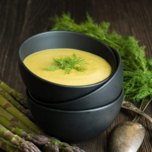 spring detox soup in bowl next to asparagus and dill weed