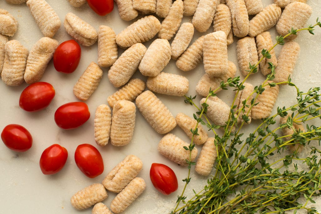 formed gnocchi next to sprigs of thyme and cherry tomatoes