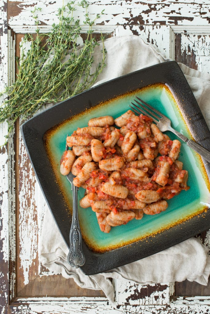 tender vegan gnocchi on plate next to springs of thyme