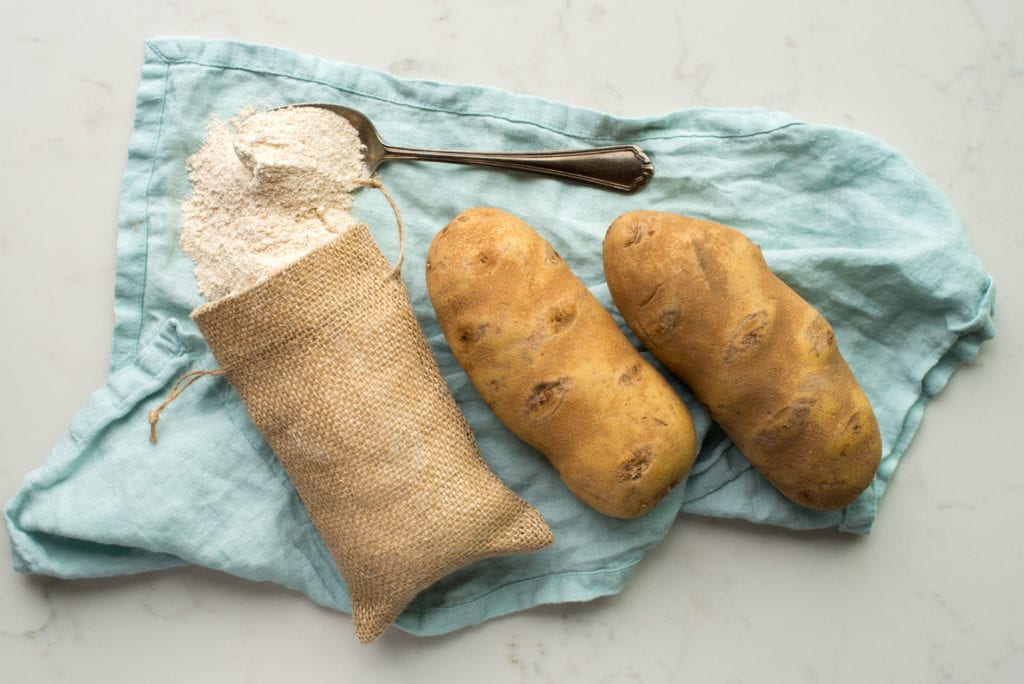 two russet potatoes and a mini bag of flour on a turquoise napkin