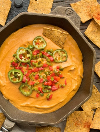 vegan cashew queso dip in cast iron pan surrounded by tortilla chips