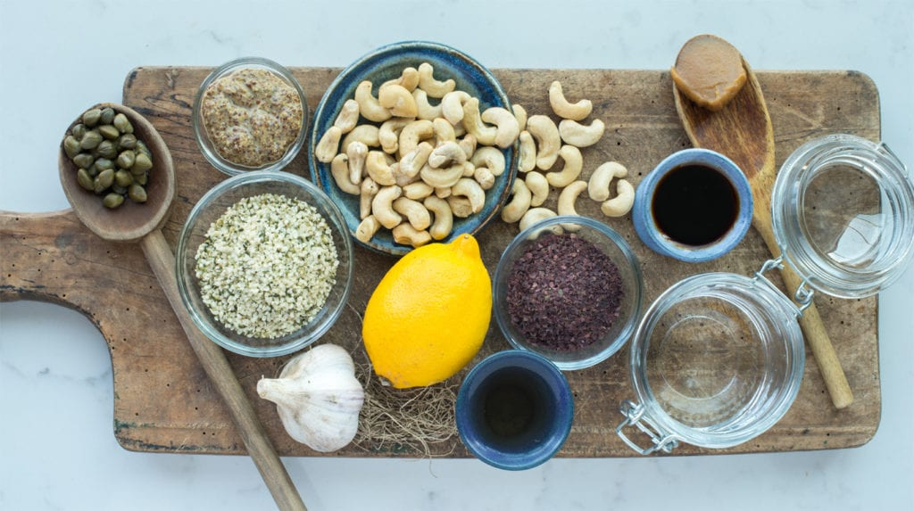 oil free caesar salad dressing ingredients in bowls and spoons on cutting board