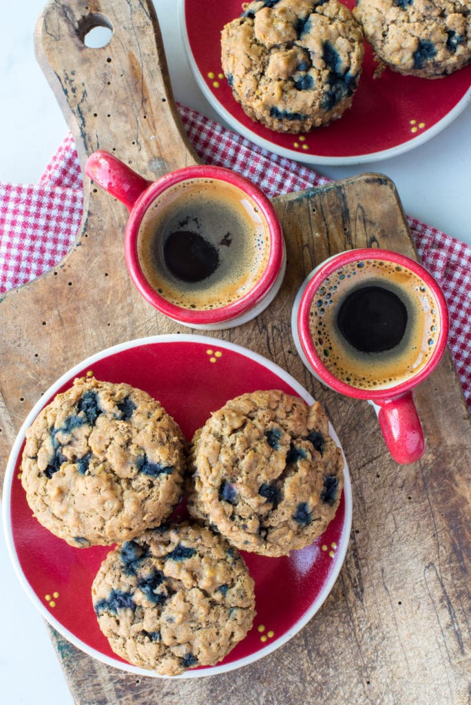 blueberry oatmeal muffins on plate next to coffee in cups