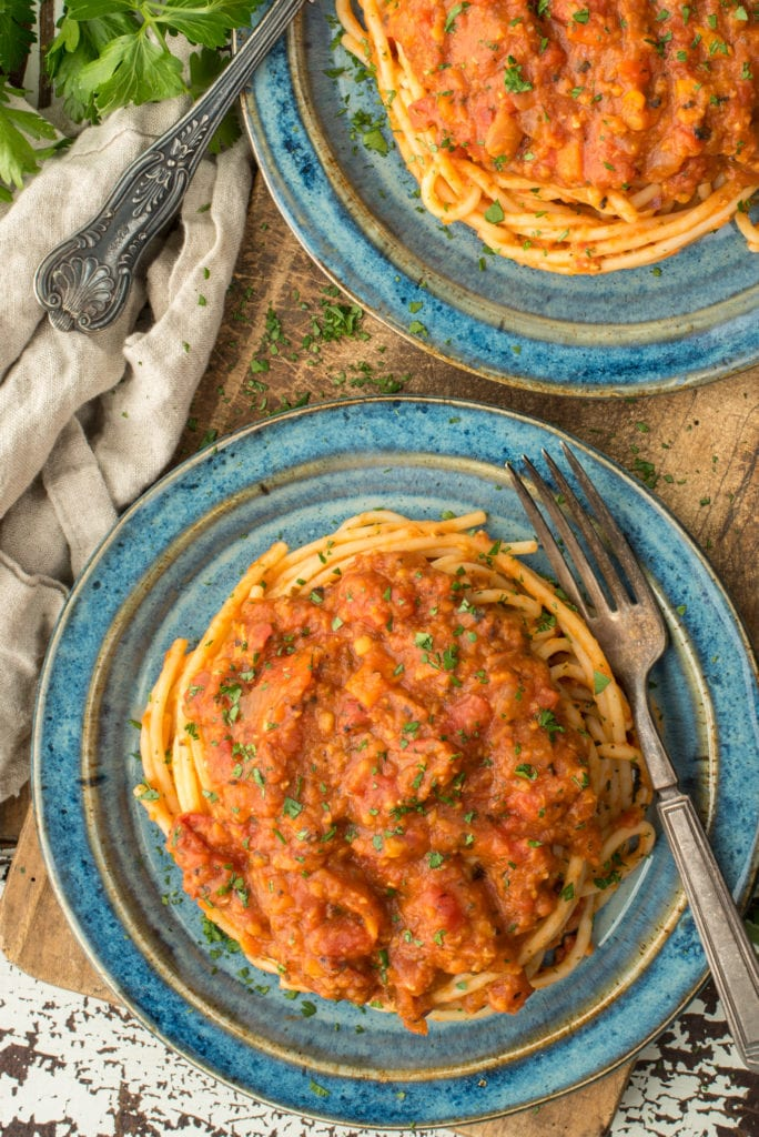 one pot lentil bolognese on spaghetti on two plates sitting on cutting board