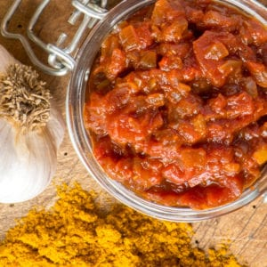 indian spiced tomato chutney in jar next to curry powder