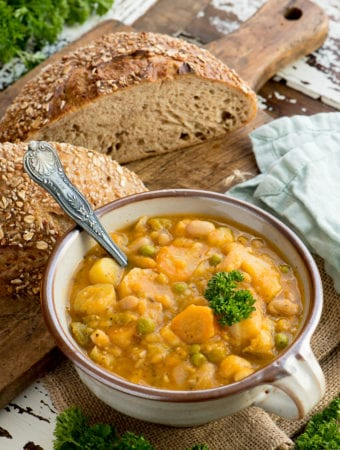 autumn vegetable stew in bowl next to sourdough loaf