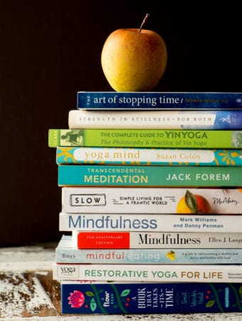 coping with anxiety books in stack with apple on top