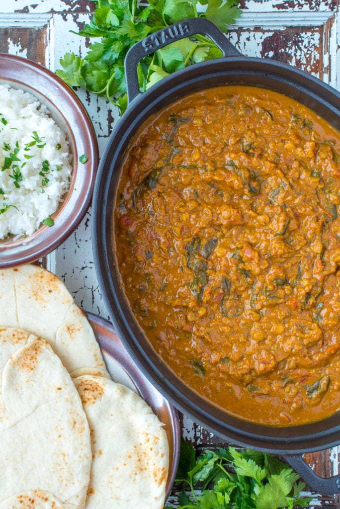 coconut lentil curry in pot next to nano bread and rice