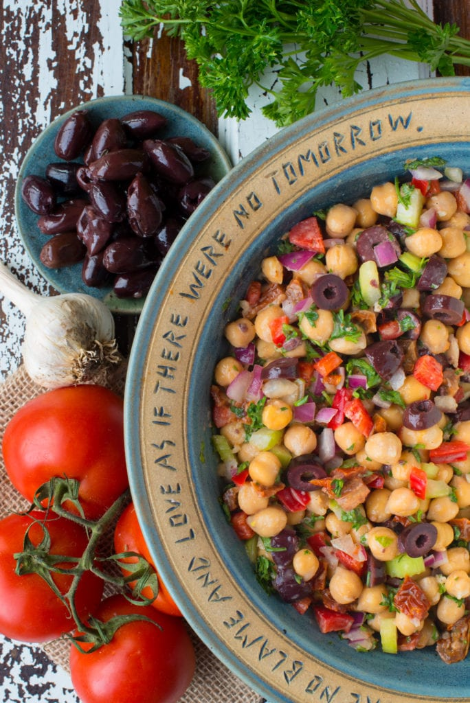greek chickpea salad in bowl next to olives and tomatoes