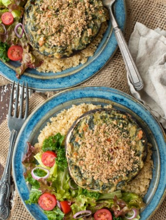spinach stuffed portobello mushrooms on plates with quinoa and salad