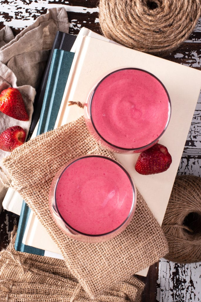 pretty in pink smoothie in two glasses on stack of books