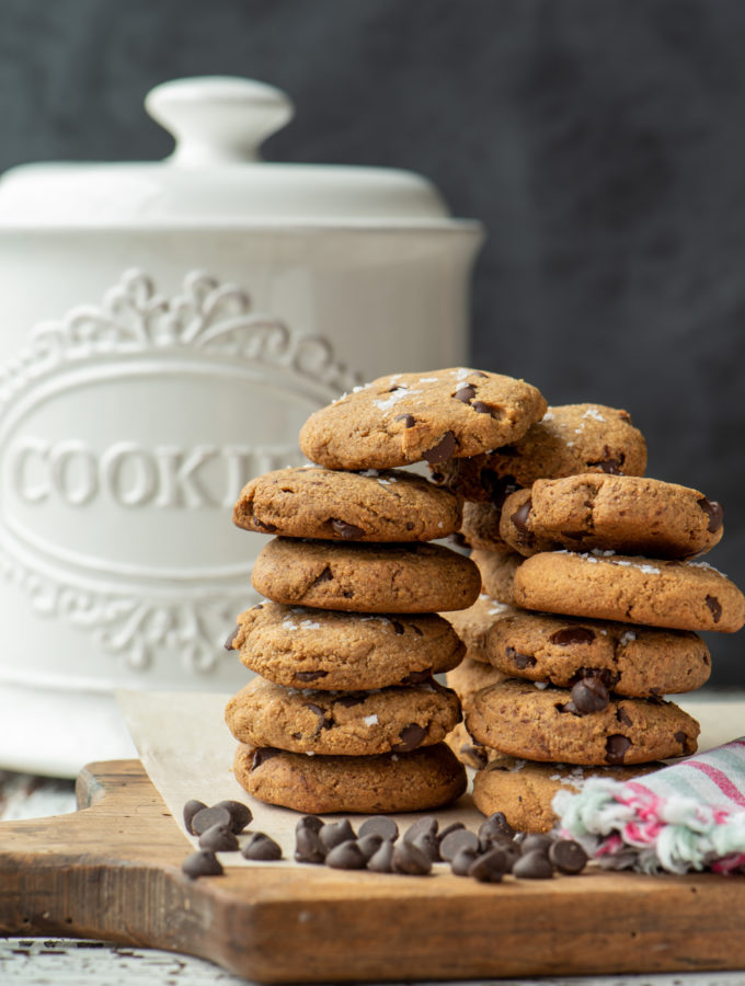 almond chocolate chip cookies stacked in front of cookie jar
