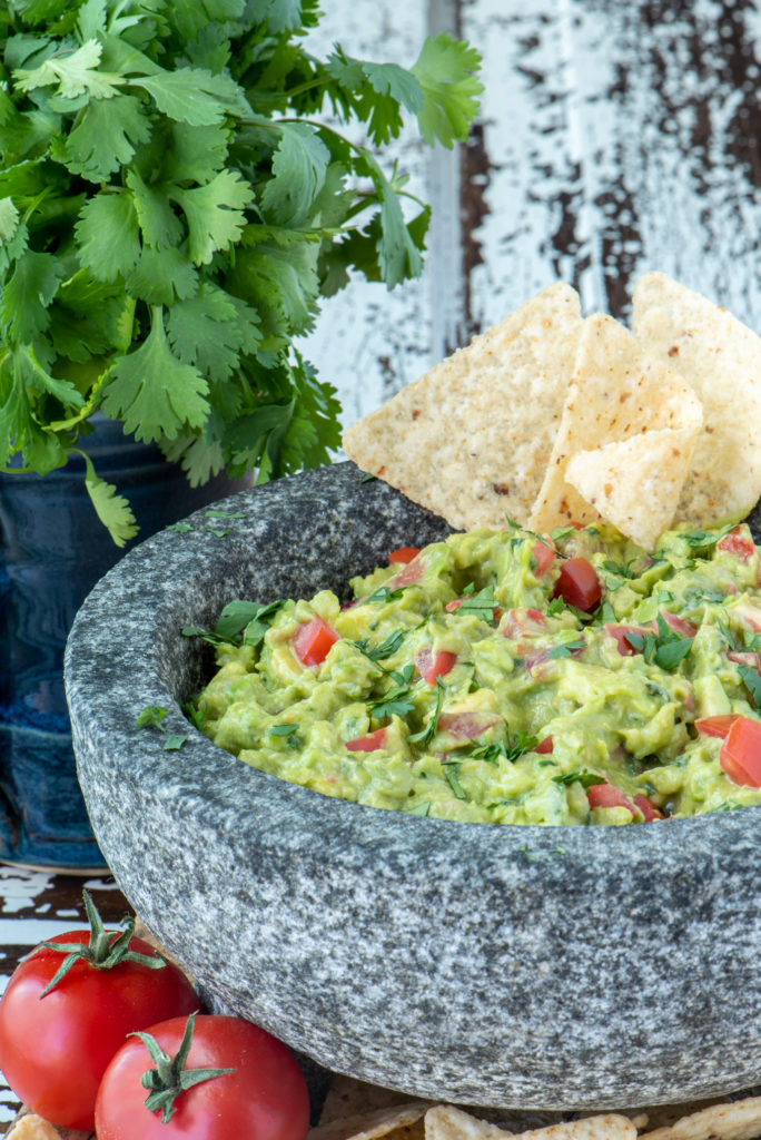 homemade guacamole in molcajete next to cilantro in cup