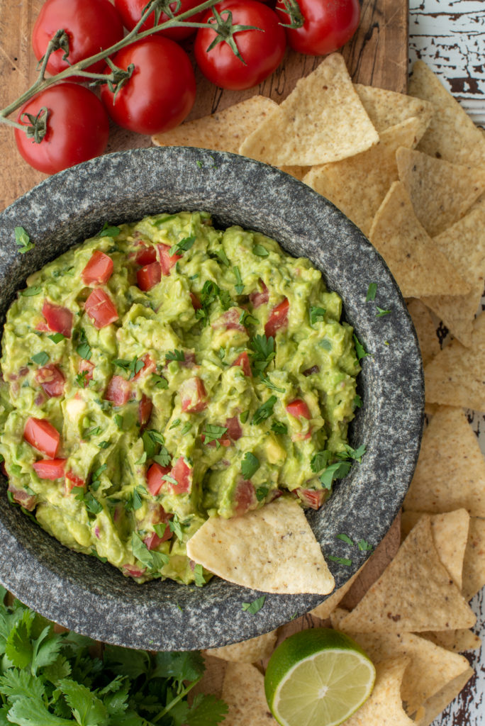 homemade guacamole in molcajete next to tortilla chips and tomatoes
