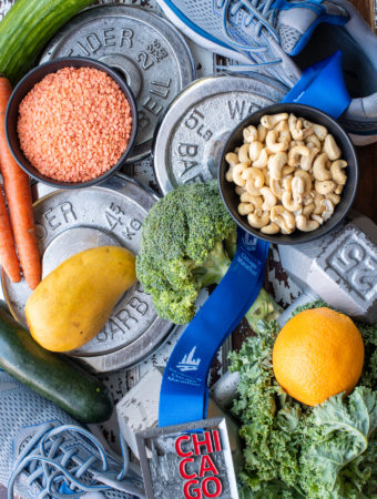 plant based athlete photo of vegetables nuts and fruit next to shoes weights and medal