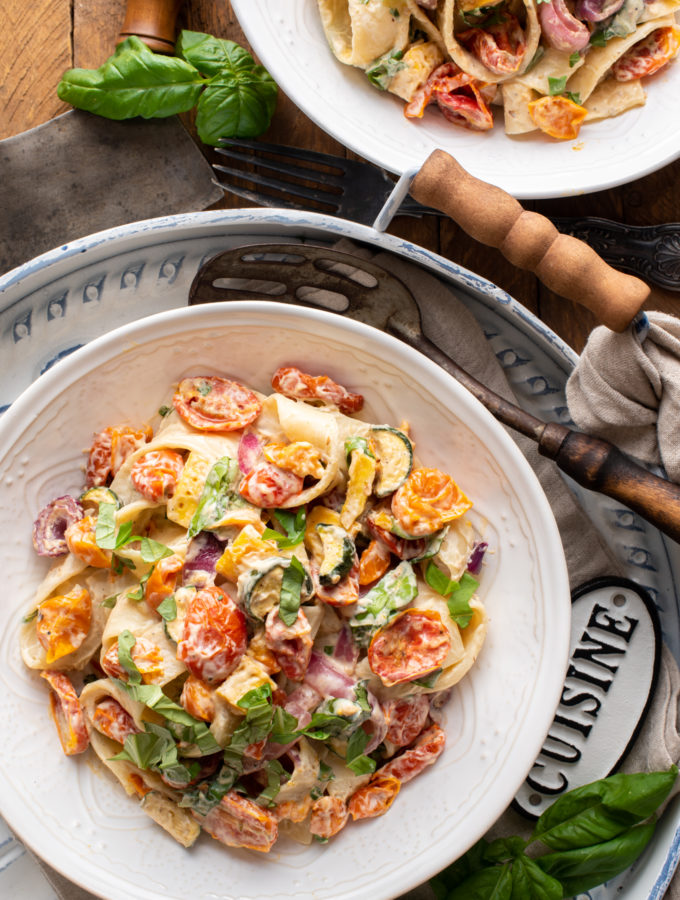 creamy roasted summer vegetable pasta in bowls