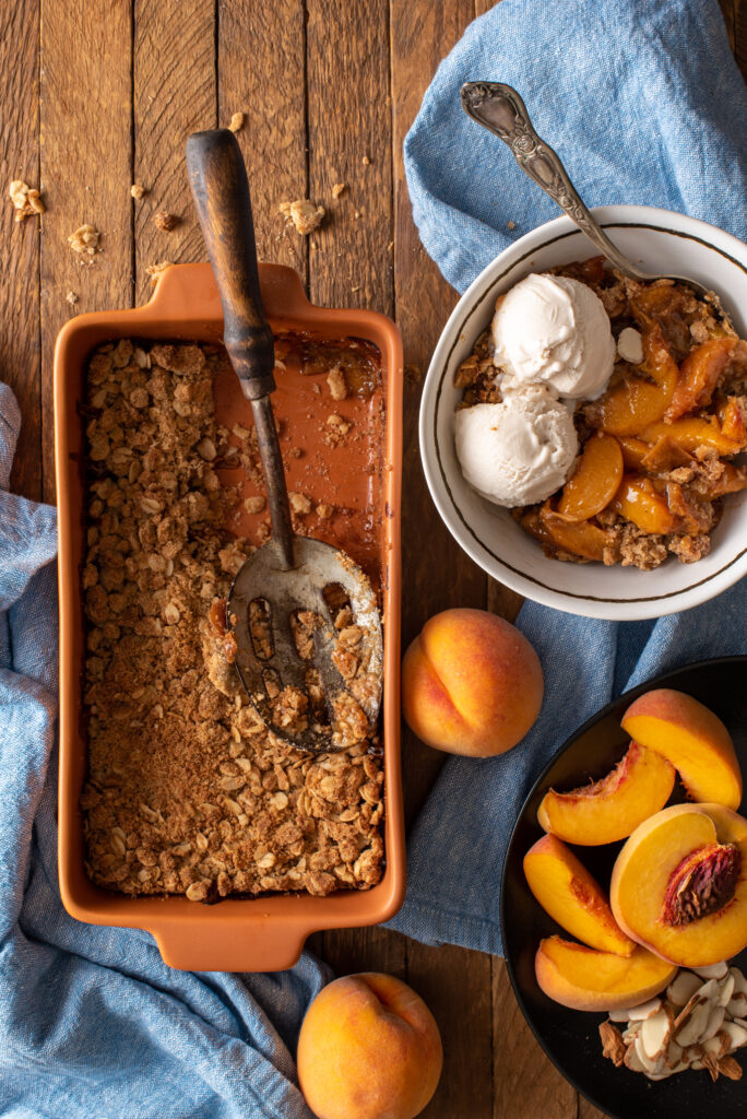 ginger peach crumble in baking dish and bowl with ice cream