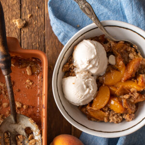 ginger peach crumble in bowl with ice cream