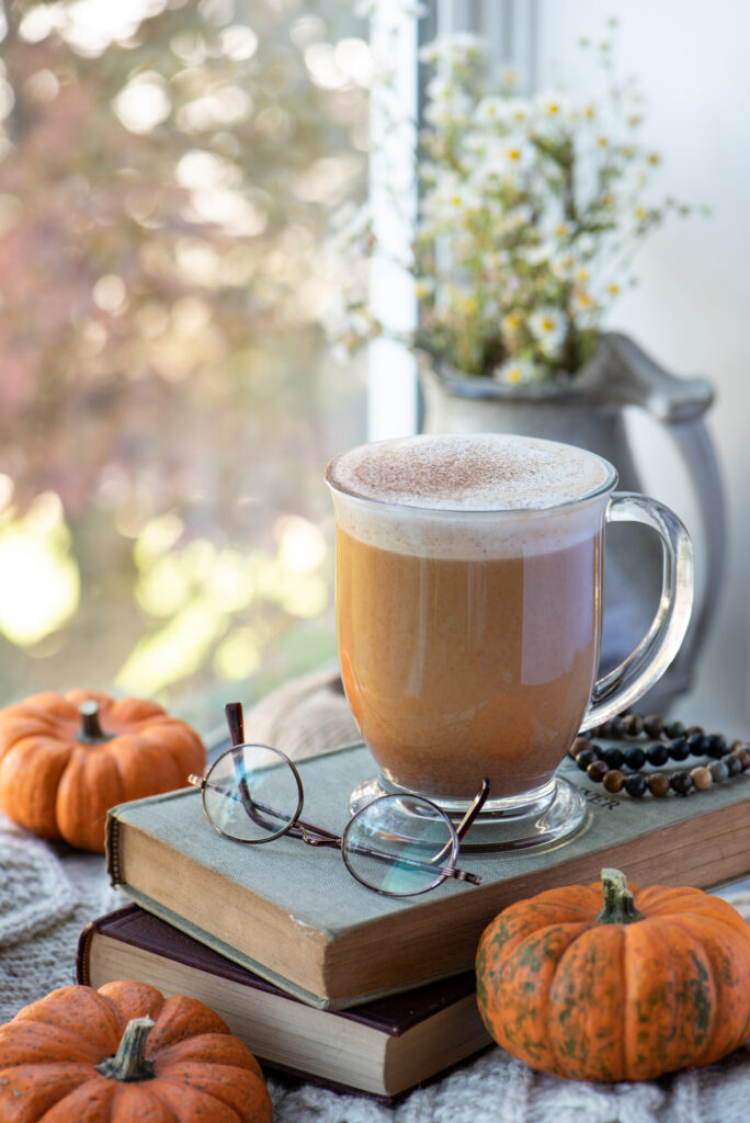 maple pumpkin spice latte in mug sitting on books