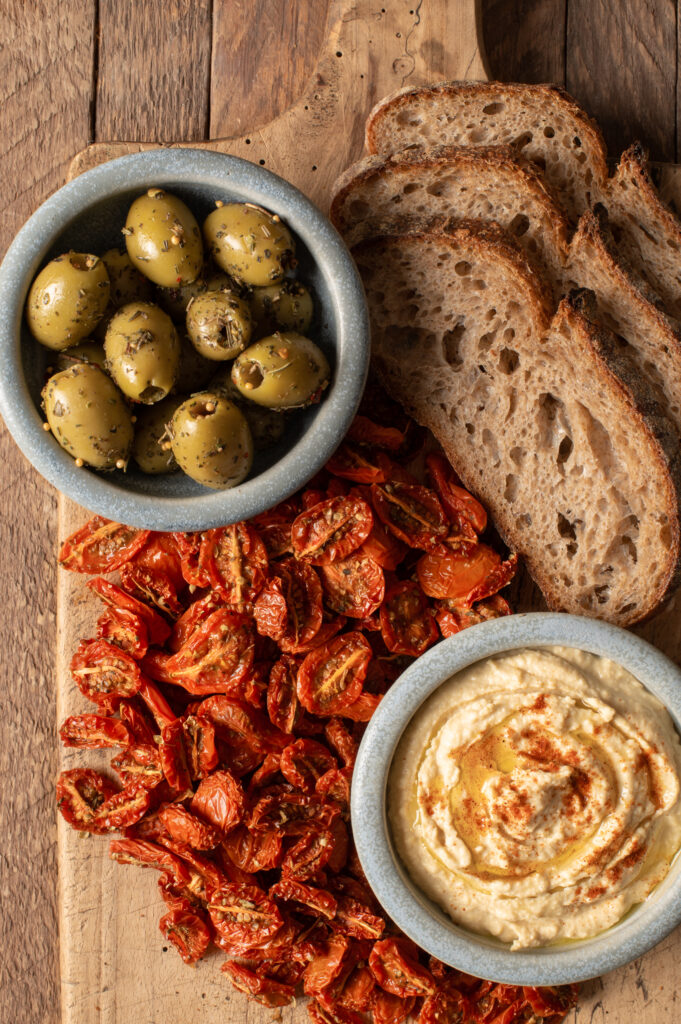 slow roasted cherry tomatoes with hummus, olives and sourdough slices on cutting board