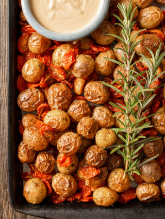 roasted potato and tomato tray bake with rosemary sprigs and tahini mustard sauce in dish
