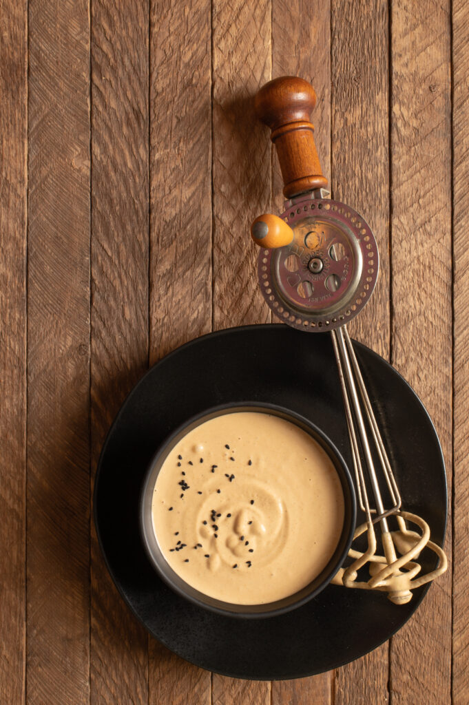 tahini mustard dressing in bowl next to hand mixer