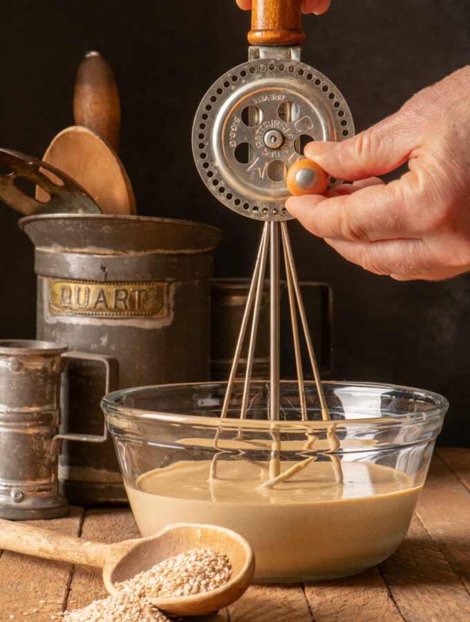 tahini mustard dressing being mixed with hand mixer in glass bowl