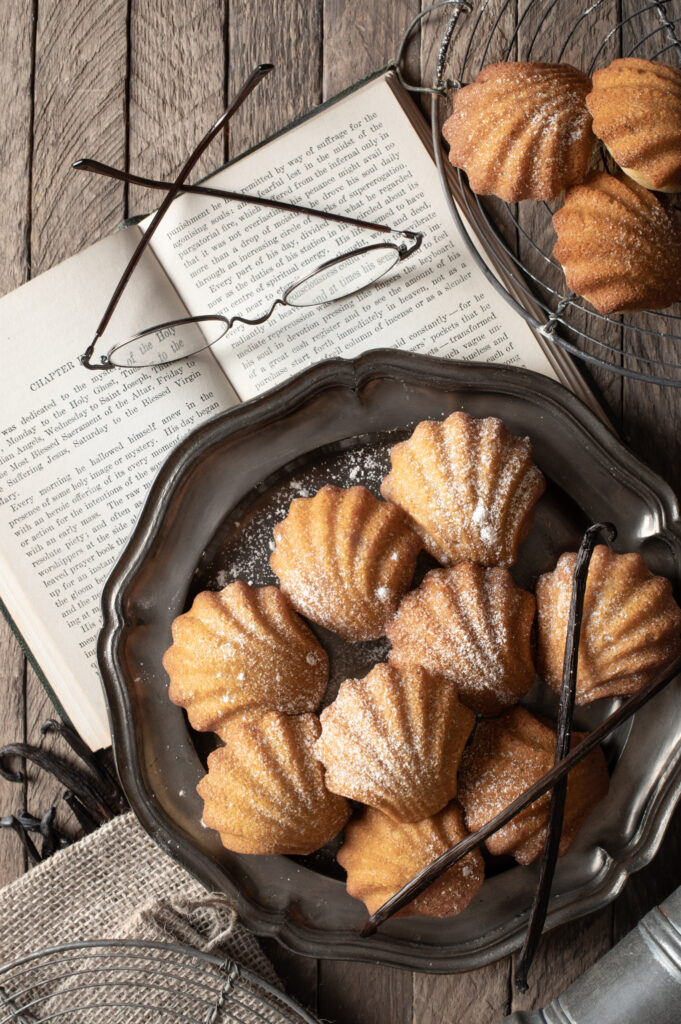 madeleines on pewter plate next to book and reading glasses