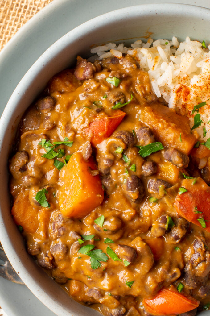 black bean and sweet potato stew with rice in pottery bowl