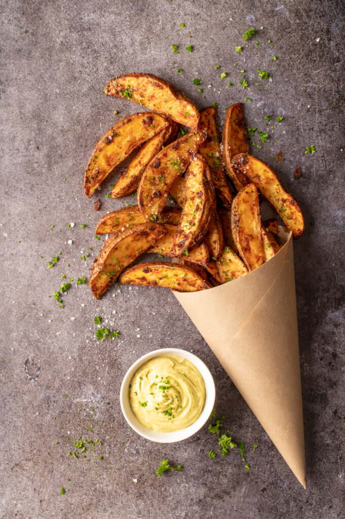 crispy oven potato wedges in paper cone next to dish of avocado mayo