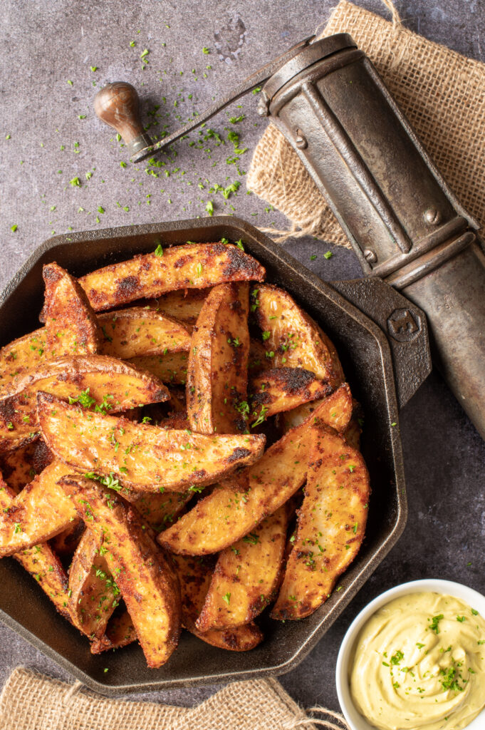 crispy oven potato wedges in skillet with small dish of avocado mayo