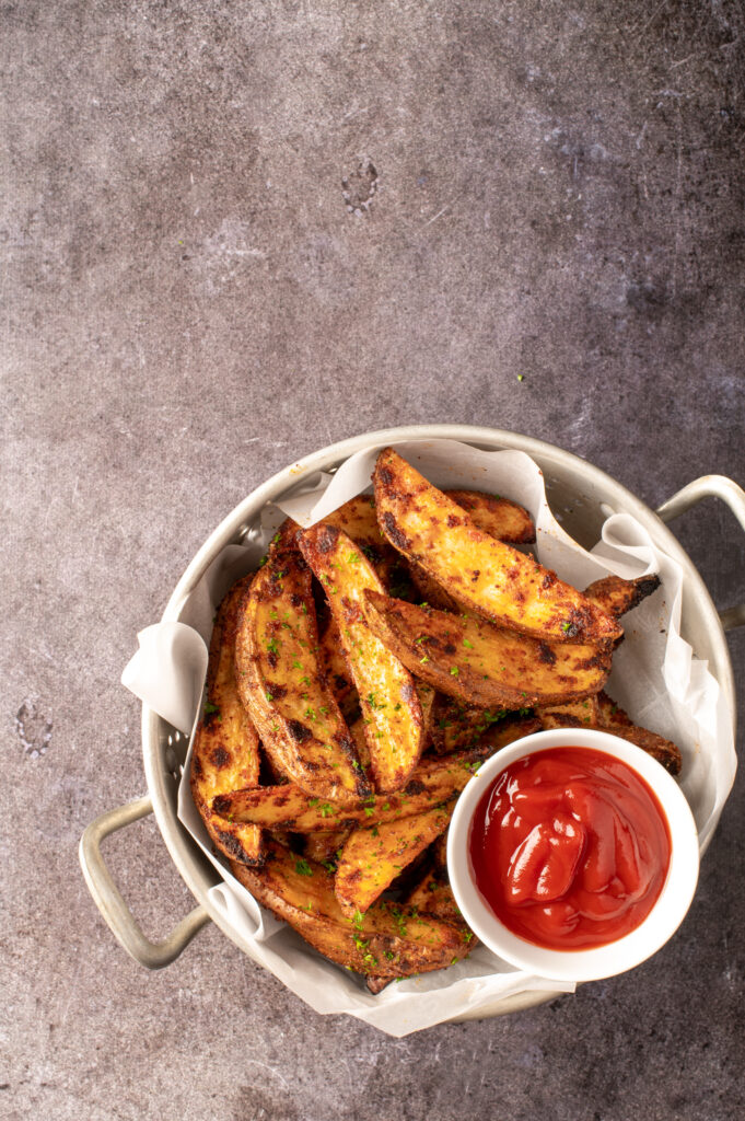 crispy oven potato wedges in colander with small dish of ketchup