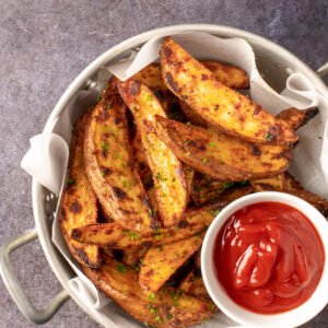 crispy oven potato wedges in colander with small dish of ketchup - recipe image