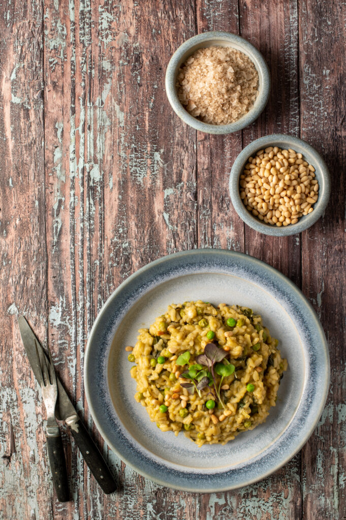 spring pesto risotto on blue pottery plate next to bowls of pine nuts and sea salt