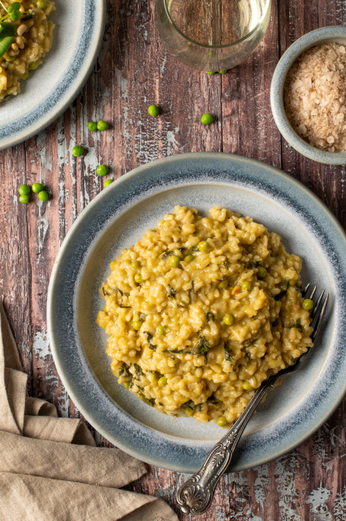 spring pesto risotto on blue pottery plate next to bowl of sea salt