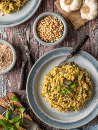 spring pesto risotto on two blue pottery plates next to bowl of pine nuts