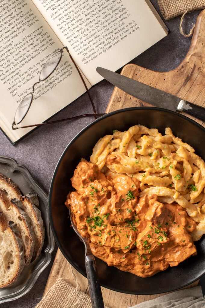 vegan hungarian tofu paprikash in black bowl on cutting board next to open book