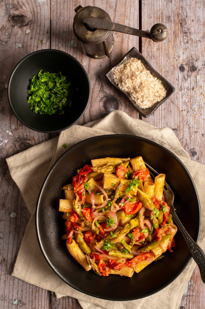 simple asparagus rigatoni in black bowl next to bowls of chopped basil and flaked salt