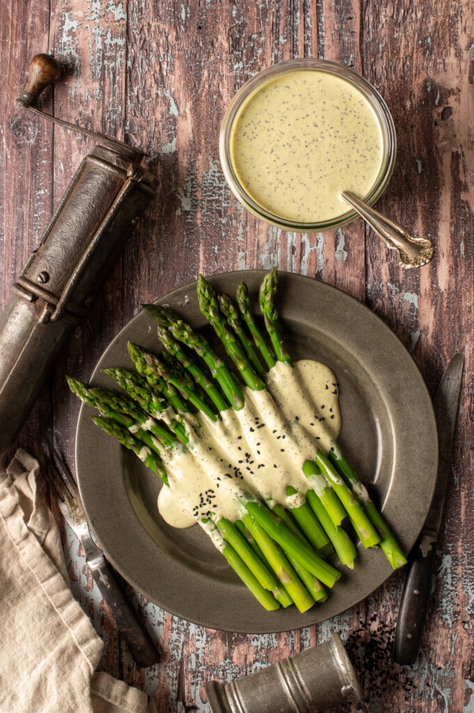 vegan lemon poppyseed drizzled over asparagus on pewter plate next to jar of dressing