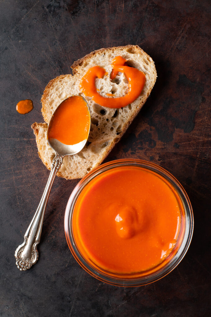 cayenne pepper hot sauce in glass jar next to piece of bread with hot sauce drizzled on it