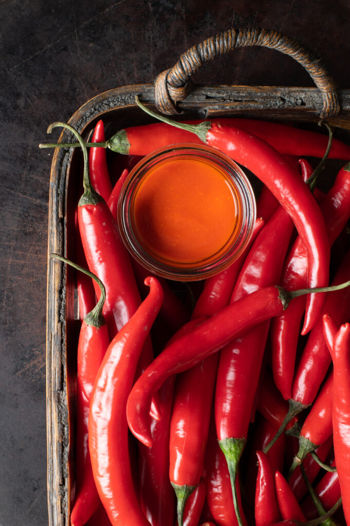 cayenne pepper hot sauce in glass jar in basket filled with fresh cayenne peppers