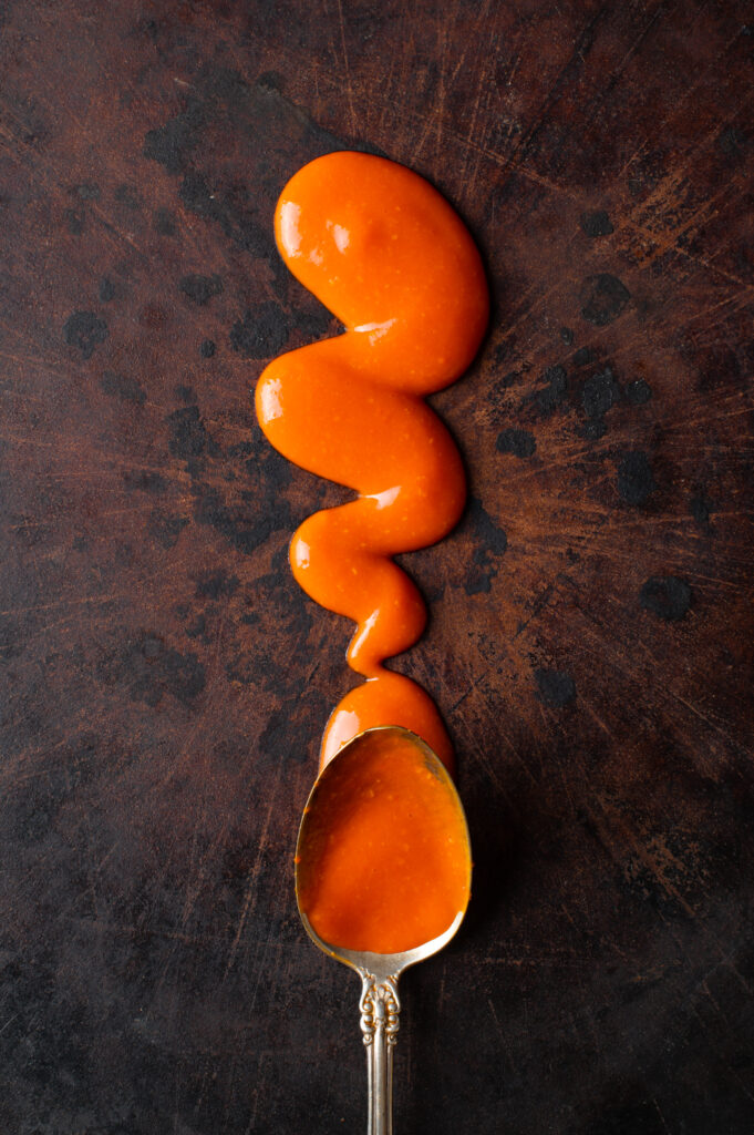 cayenne pepper hot sauce drizzled on stone baking sheet
